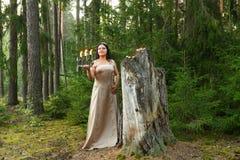 Une fée de forêt dans des vêtements blancs avec un chandelier a allumé des bougies dans la forêt photo stock