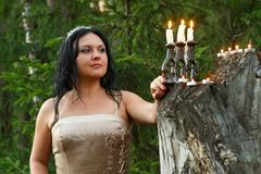 Une fée de forêt dans des vêtements blancs avec un chandelier a allumé des bougies dans le plan rapproché de forêt photographie stock libre de droits