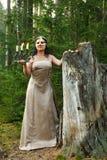 Une fée de forêt dans une robe légère dans une forêt avec un chandelier avec des bougies image libre de droits
