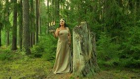 Une fée de forêt dans un masque d'or sur son visage se tient à un grand tronçon et tient un chandelier avec des bougies dans sa m clips vidéos