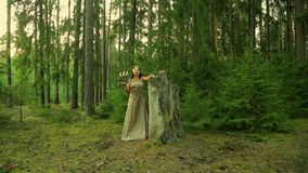 Une fée de forêt dans un masque d'or sur son visage tient un chandelier avec des bougies dans sa main clips vidéos