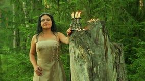 Une fée mystérieuse dans les bois se tient à un grand tronçon avec des bougies banque de vidéos