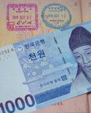 Une facture coréenne de 1.000 a gagné des repos sur un passeport russe avec des timbres d'entrée et de sortie Photo stock