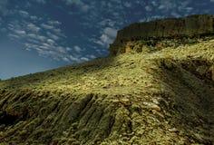 Une falaise ombragée contre un ciel bleu-foncé Image stock