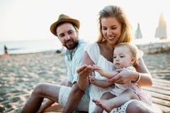 Une famille avec une fille d'enfant en bas âge s'asseyant sur la plage de sable des vacances d'été photographie stock libre de droits