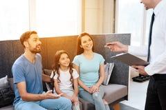 Une famille avec une petite fille s'assied sur le sofa dans un magasin de meubles Image libre de droits