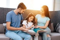 Une famille avec une petite fille s'assied sur le sofa dans un magasin de meubles Photo libre de droits
