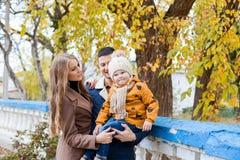 Une famille avec un garçon marchant dans le bonheur de parc d'automne Photographie stock libre de droits