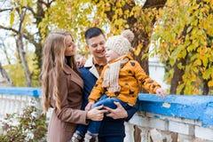 Une famille avec un garçon marchant dans le bonheur de parc d'automne Photo stock