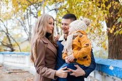 Une famille avec un garçon marchant dans le bonheur de parc d'automne Photos stock