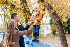 Une famille avec un jeune garçon dans la promenade de forêt d'automne Image libre de droits