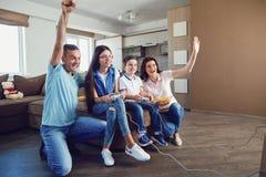 Une famille gaie joue des jeux vidéo dans la maison Images libres de droits