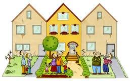 Une famille heureuse devant leur maison neuve Photos stock