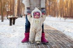 Une famille heureuse La mère enseigne un enfant à marcher en parc d'hiver Image stock