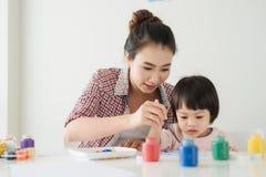 Une famille heureuse peint La maman aident son dessin de fille Photo libre de droits