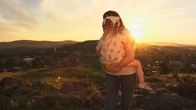 Une famille heureuse sur le coucher du soleil, mère tient sa fille dans des ses bras banque de vidéos