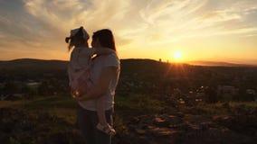 Une famille heureuse sur le coucher du soleil, mère tient sa fille dans des ses bras clips vidéos