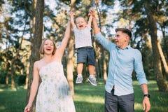 Une famille mignonne - la maman, le papa et le fils passent le temps d'amusement en nature image stock