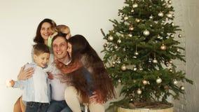 Une famille nombreuse avec trois enfants étreint près de l'arbre de nouvelle année an neuf heureux de Noël joyeux clips vidéos