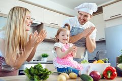 Une famille prépare la nourriture des légumes dans la cuisine photo libre de droits