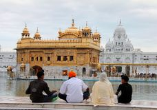 Une famille priant devant le temple d'or Images libres de droits