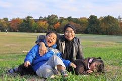 Une famille se trouvant et s'asseyant sur l'herbe pendant l'automne photo stock