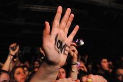 Une fan avec l'amour de mot sur sa main au clinquant Photographie stock libre de droits