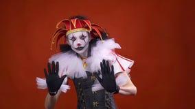 Une farceuse de femme avec le maquillage blanc et noir sur son visage exécute l'exposition de pantomime banque de vidéos