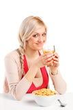 Une femelle buvant d'un jus et mangeant des cornflakes Photo stock