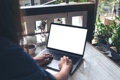Une femme à l'aide de l'ordinateur portable avec l'écran de bureau blanc vide avec la tasse de café sur la table Image stock