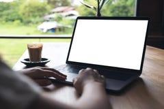 Une femme à l'aide de l'ordinateur portable avec l'écran de bureau blanc vide avec la tasse de café sur la table en bois Photographie stock libre de droits