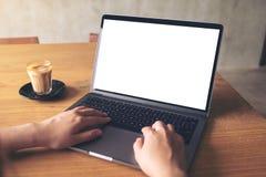 Une femme à l'aide de l'ordinateur portable avec l'écran de bureau blanc vide avec la tasse de café sur la table en bois Photo libre de droits