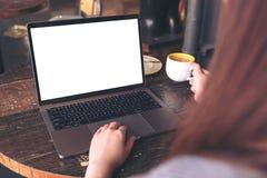 Une femme à l'aide de l'ordinateur portable avec l'écran de bureau blanc vide tout en buvant du café chaud sur la table en bois e Image libre de droits