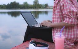 Une femme à l'aide de l'ordinateur portable tout en se reposant près de la rivière photo libre de droits