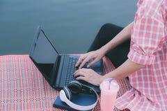 Une femme à l'aide de l'ordinateur portable tout en se reposant près de la rivière photographie stock libre de droits