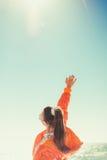 Une femme à l'arrière-plan de la mer dessine sa main au ciel Vue arrière Images libres de droits