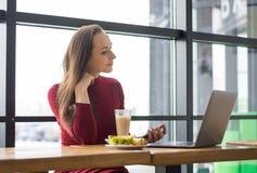 Une femme à un déjeuner avec un téléphone portable avec l'ordinateur portable en café Images libres de droits