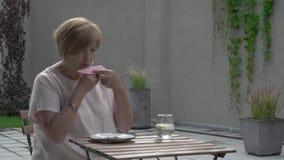 Une femme âgée finit de manger un gâteau Elle s'assied dehors dans la terrasse Elle essuie ses lèvres et boit une certaine eau banque de vidéos