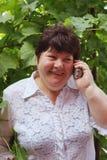 Une femme âgée parle par le téléphone Photographie stock libre de droits