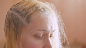 Une femme éclaire ses racines du poil à la maison utilisant une huile de blanchiment avec une brosse banque de vidéos
