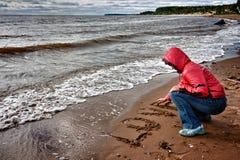 Une femme a écrit dans le sable Photographie stock