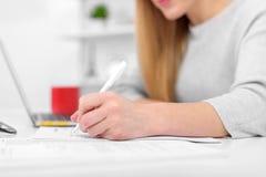 Une femme écrit tout en se reposant à une table dans un bureau ou une salle de classe La fille remplit documents sur le lieu de t photos stock