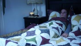 Une femme éprouvant la paralysie de sommeil dans la chambre à coucher foncée banque de vidéos