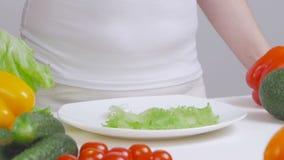 Une femme éteint des feuilles de laitue de vert sur un plat blanc tout en faisant cuire un déjeuner végétarien banque de vidéos