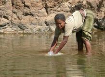 Une femme éthiopienne inconnue lave en rivière dans Roby, Ethiopie - 23 novembre 2008. Images libres de droits