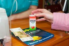Une femme achète Corvalol dans la pharmacie Images stock