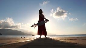 Une femme adulte avec une écharpe se tient sur la plage au lever du soleil au ralenti clips vidéos