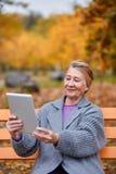Une femme adulte en parc d'automne s'assied sur un banc avec un comprimé et sourit Image stock