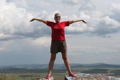Une femme adulte se tient, des bras tendus, sur une haute montagne, contre le contexte d'une plaine et d'un ciel nuageux images libres de droits