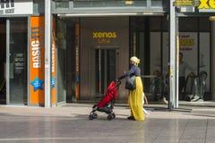 Une femme africaine portant une voiture d'enfant Photo stock